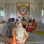Inside of Babaji's shrine, pilgrims sit in meditation before completing the climb to the cave.